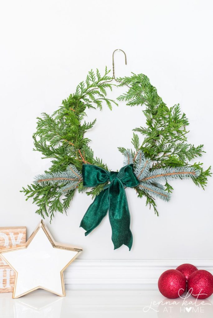 This DIY Simple Greenery Wreath using a coathanger form is on of my 12+ favorite Christmas Wreath tutorials. Learn how to make wreaths to decorate your home, everywhere from your front door to your kitchen! The wreaths use everything from fresh evergreens to this coathanger (a genious way to save money when you make your wreath. You gotta see how it's done!) and everything in between. Check it out to get some fabulous ideas.