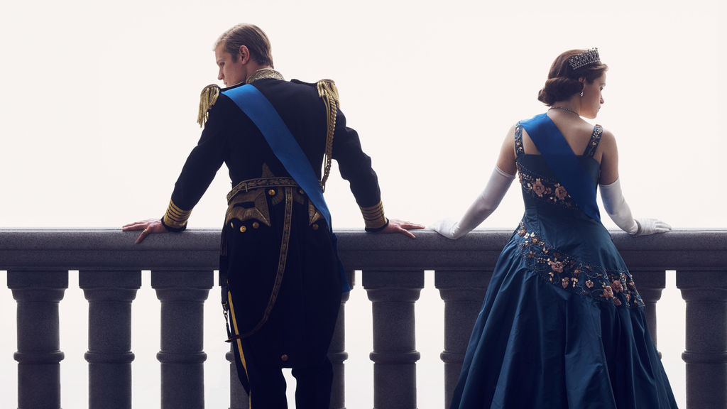 Claire Foy and Matt Smith as Queen Elizabeth II and Prince Phillip on the balcony in Netflix The Crown - Fans of the Crown will love these movies and other series about the British Royal Family and other royalty. They also make great gifts for fans of The Crown!