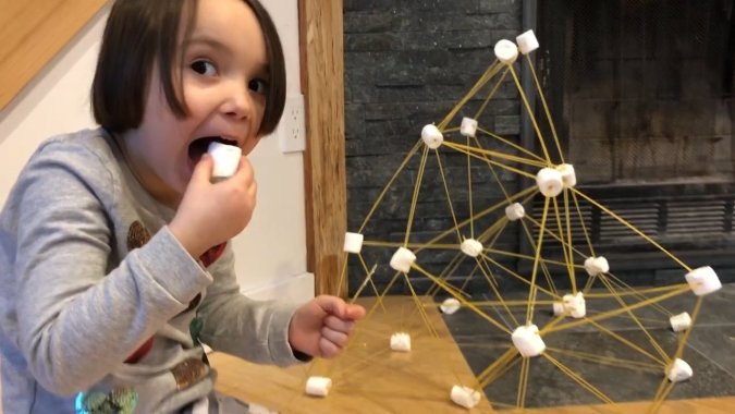 girl eating a marshmallow while building a tower on a snow day activity indoors