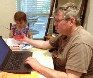 Dad working from home on computer while child paints his hand why dads matter momcavetv