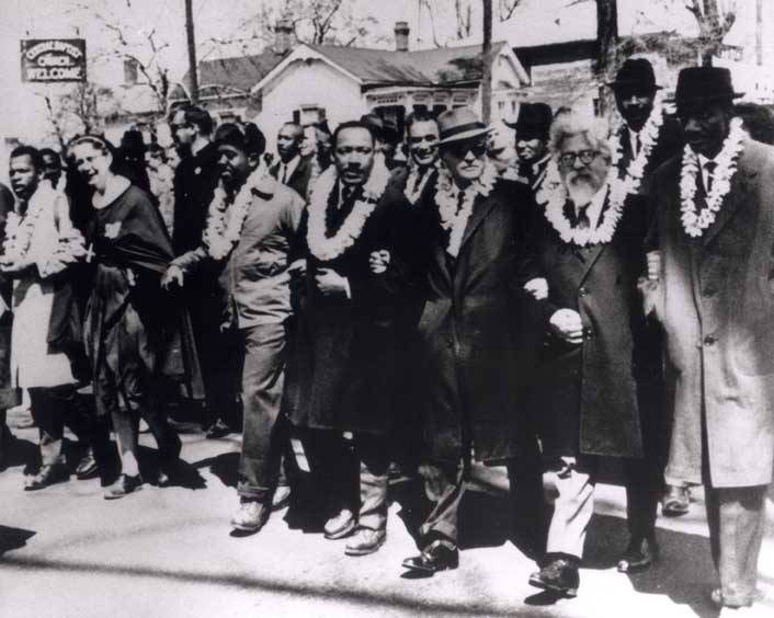 Martin Luther King Jr. walks arm in arm with others leaving Brown's A.M.E Church in Selma