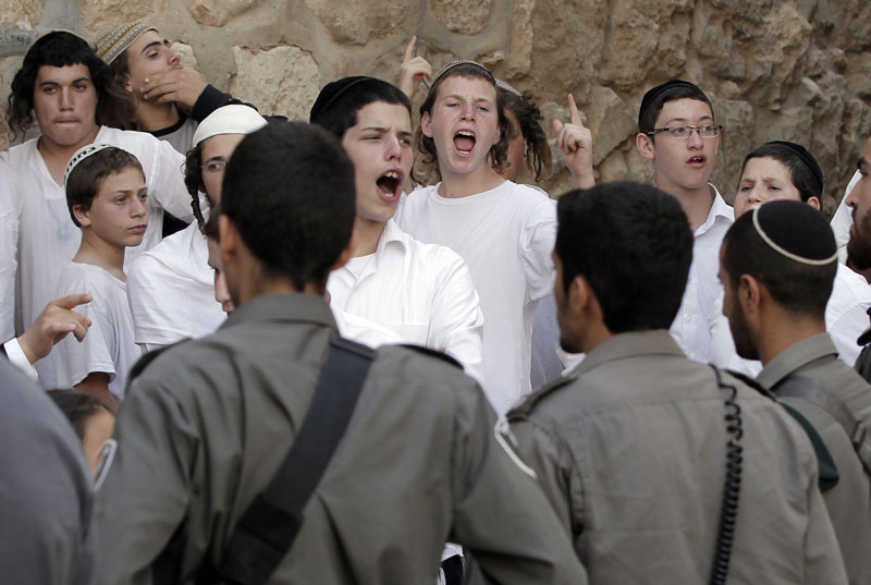 Ultra-Orthodox Jewish youth are surrounded by Israeli police as they heckle Catholics exiting the Cenacle after the Pentecost prayer in 2015. © Getty