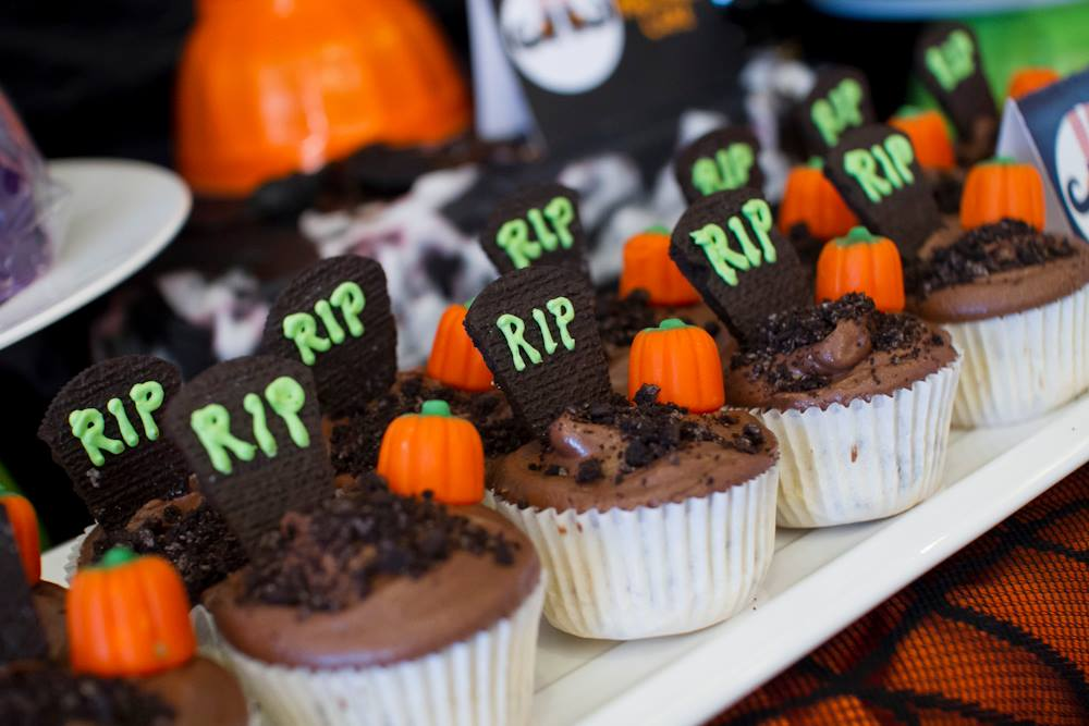 Vanilla Cupcakes with Oreo bits mixed in the batter topped with Chocolate Buttercream Icing, a Pumpkin Cream, and more Oreos for dirt and a tombstone.