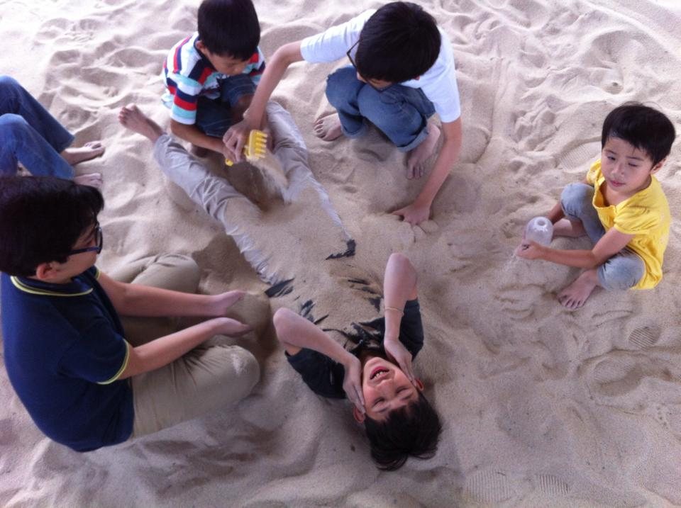 Like this one taken by Michelle Lim, which clearly shows my son's affinity for the sand...so much so, that he didn't mind being covered...completely.
