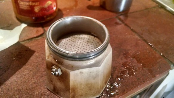 The base of the mocha pot with the empty coffee filter resting in it.