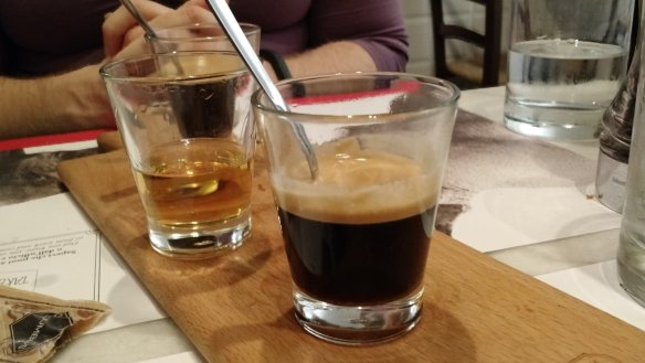 An espresso served in a tiny glass. Glass of grappa behind.