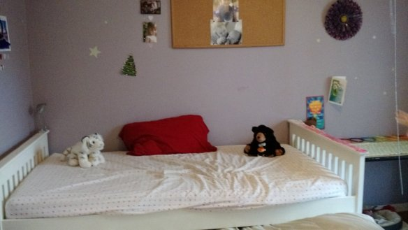 Her upper bed with stuffed animals ready to welcome one of their kind.