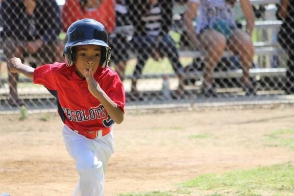 Boy running bases, baseball game