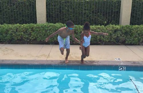 Brother and sister jump in the pool together