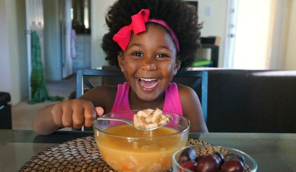 Beautiful happy girl enjoying her soup