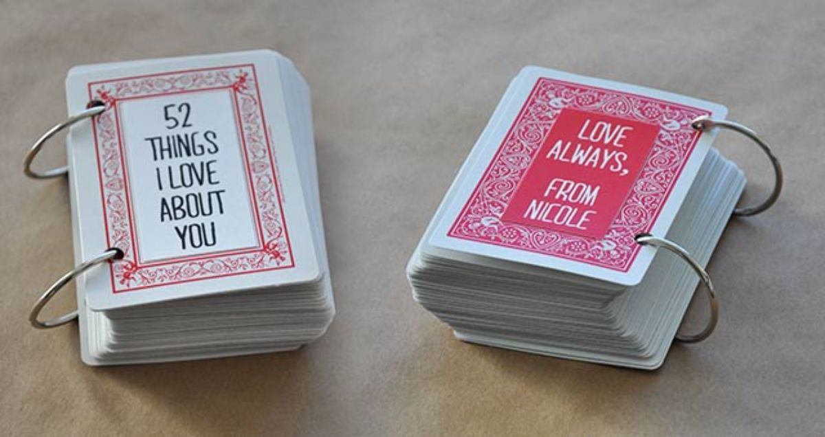 "in na cream background sit two playing card sized ringbound books. On the front the text reads ""52 Things I love about you"" and ""Love always, from Nicole"""