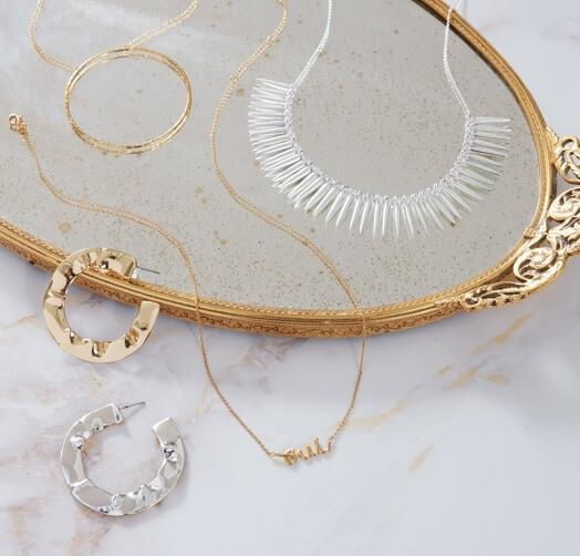 Photo of the MODERN CLASSICS $99 ($226 value) kit showing two necklace, earrings, and bracelet on a mirror tray on a white marble background.