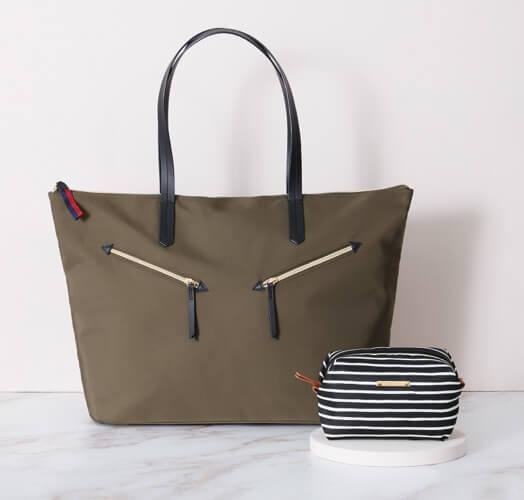Photo of GIRL ON THE GO $59 ($163 value) set showing a brown bag with handles and zippers, with a small striped pouch. Both are sitting on a white marble surface with white background.