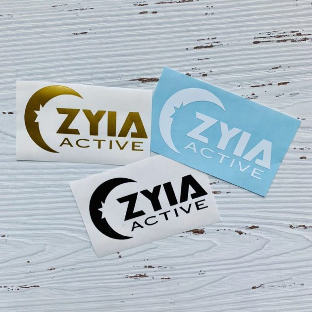 Photo of Zyia Active logo printed stickers sitting on a white wooden background. Stickers have various colors including golden, black and white with blue background.