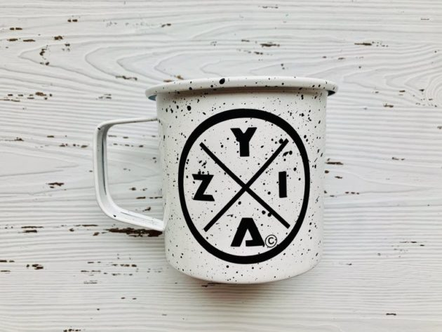Photo of a white tin mug sitting on a white wooden background. Mug has the letters Z Y I A printed on it in black.
