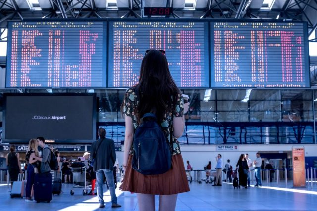A girls standing next to a board on an airport looking for flighst