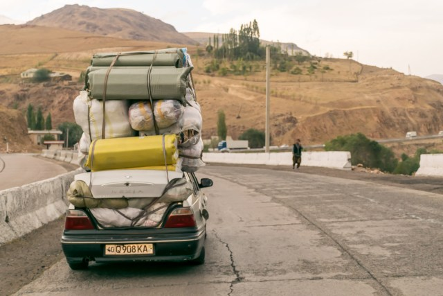 Small car carrying a pile of stuff on top of it