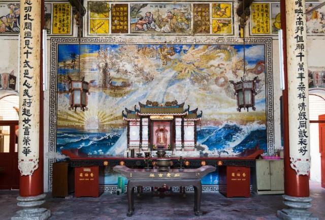dentro de um templo budista, com inscrições chinesas