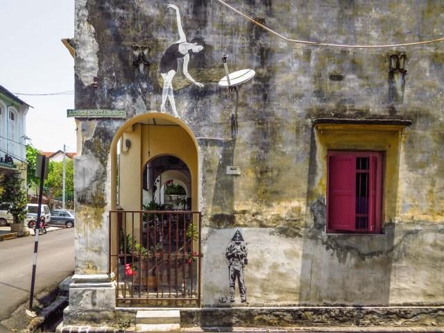 entrada de uma casa com um grafite de uma bailarina ao lado da janela