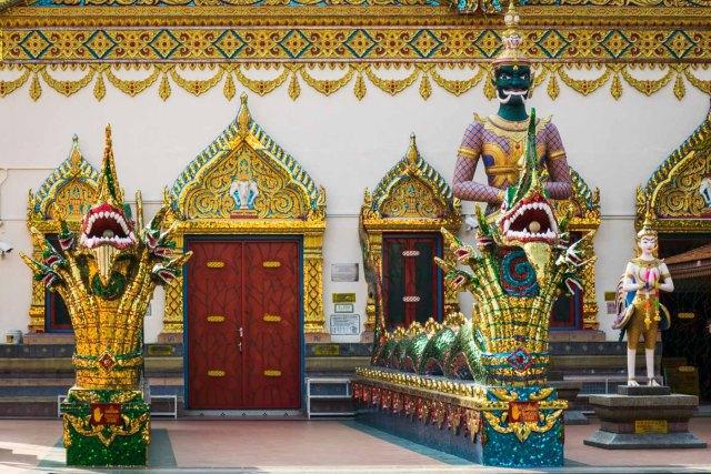 a entrada de um templo budista com estátuas de dragões