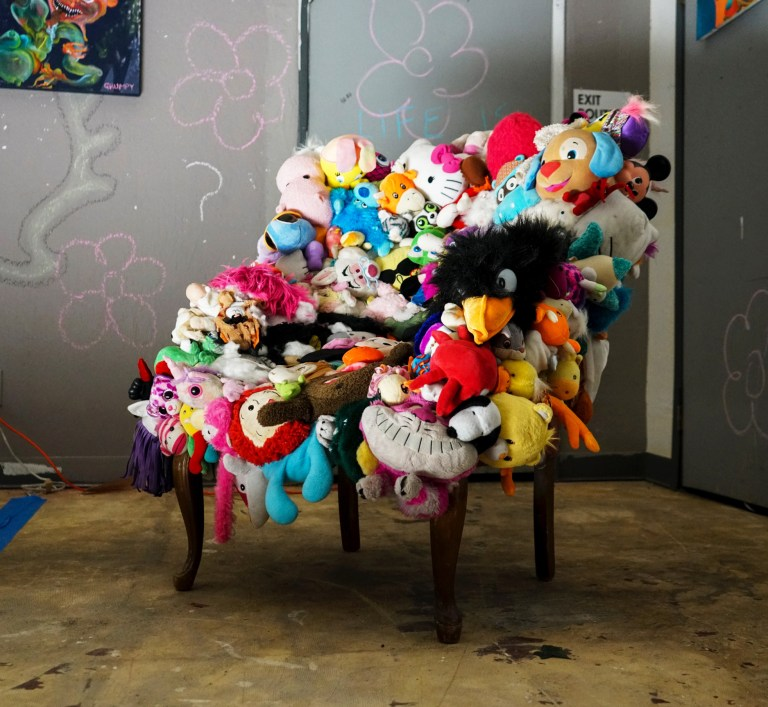 A picture of a sofa chair made of the heads of 300 stuffed animals.