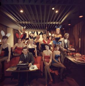 Working at his typewriter surrounded by 'bunny girls', publisher Hugh M Hefner at the Playboy Key Club in Chicago. He founded adult magazines, Playboy, VIp and Oui. (Photo by Slim Aarons/Getty Images)