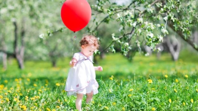 Baby Girl With Red Balloon Outside Field