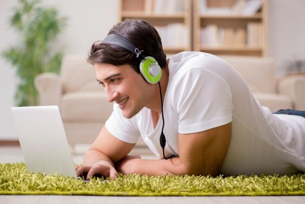 Young man lying on floor listening to music on laptop