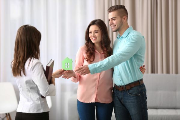 Mortgage broker handing house model to couple