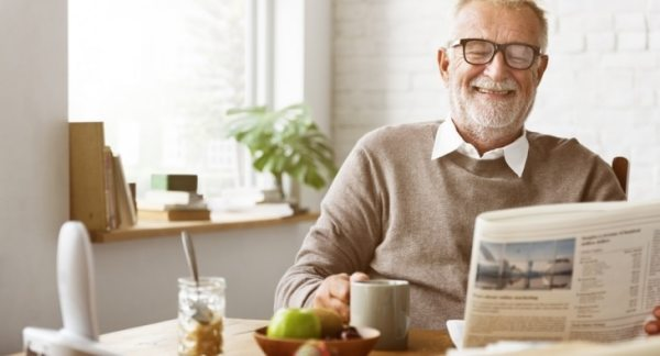 Old man sat at the kitchen table reading newspaper