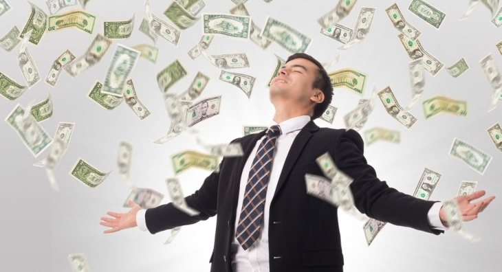 Businessman with money raining down around him
