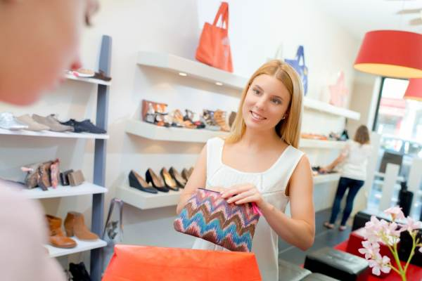 Woman smiling while getting money out of a purse to pay in a shop
