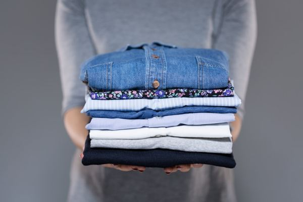 Woman holding a pile of folded clothing