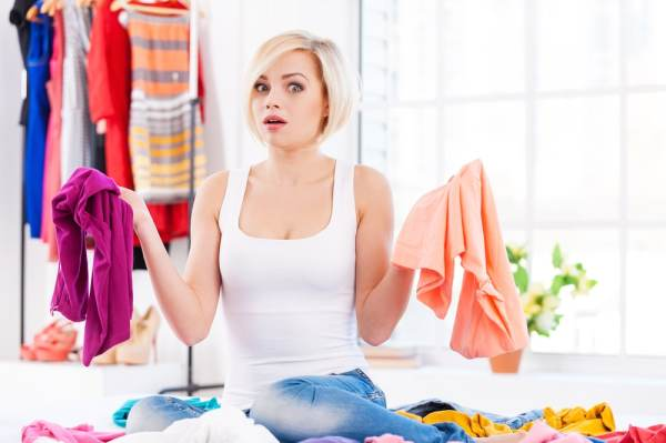 Woman holding clothes and looking confused
