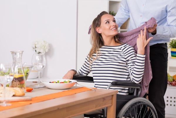 Disabled woman in wheelchair at kitchen table