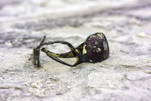 Broken sunglasses in the sand