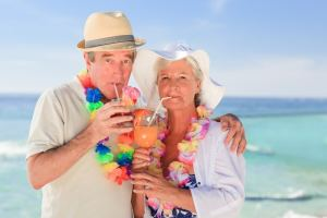 Elderly couple wearing leis and drinking cocktails on the beach