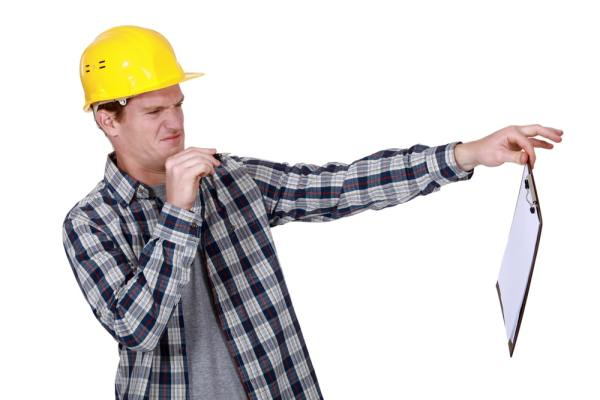 Suspicious builder unwilling to sign a contract on a clipboard