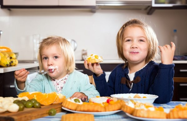 Little girls happily eating cakes