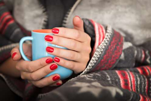 Woman holding mug of warm drink wrapped in blanket