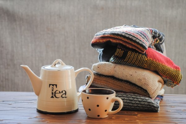 Tea pot and cup beside pile of kitted wooly jumpers