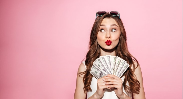 Happy young woman holding money and pulling a silly face
