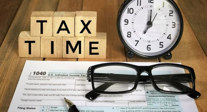 Pen and glasses ready to complete tax return in time