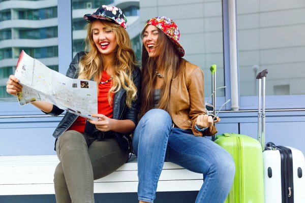 Young women using a map at the airport