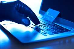 Gloved hand typing on laptop with stolen credit card propped against the screen