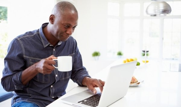 Middle aged man using Laptop and drinking from a mug