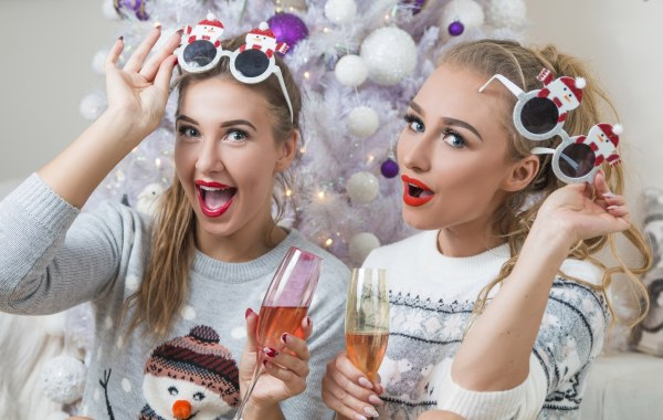 Women wearing silly christmas jumpers and glasses