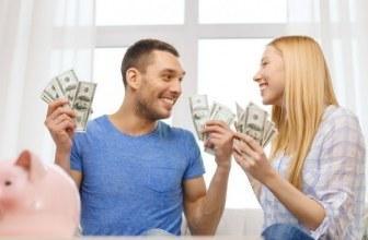 Couple celebrating with large handfuls of money