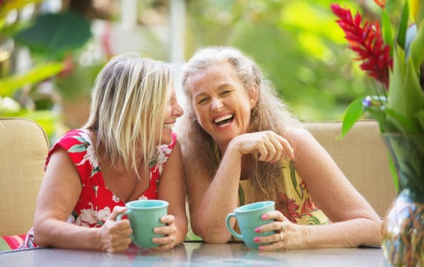 Older friends laughing over hot drinks