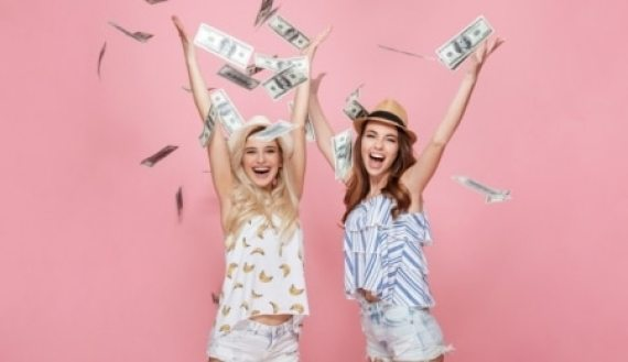 Young women showing cash in the air